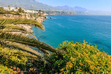Balcon of Europe on the Spanish coast of Nerja. View of a small stretch of beach on the Costa del Sol from the Mediterranean Sea with a blue sky. In the background mountains and buildings of a village