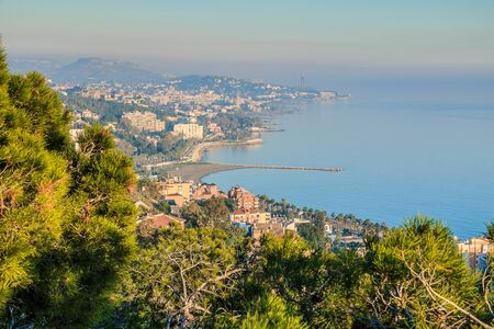 Panoramic view of the Spanish coast in Nerja from the Balcon de Europa. Sunny autumn day on the Mediterranean Sea with a view of a village and hills on the horizon. Blue sky with clouds and palm trees in the foreground