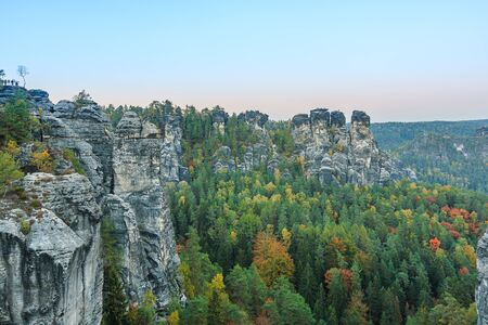 View of rock formation in the National Park of Saxony. Saxon Switzerland in autumn in the evening. Rocks, forests and trees in the valley with a view from the Bastei bridge in autumn mood