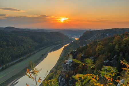 View from Bastei bridge over the Elbe valley in the Saxon Switzerland National Park. River Elbe at sunset. Colorful sky with orange sun. Landscape with rocks, trees and forests in autumn mood 版權商用圖片