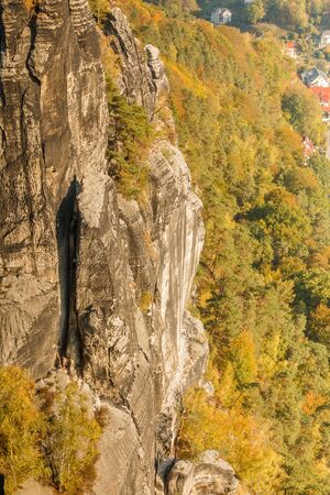 Rock formation in the Elbe Sandstone Mountains in autumn. Sunshine and trees with the Elbe valley. Climbing and hiking near the Bastei bridge in Saxon Switzerland 版權商用圖片