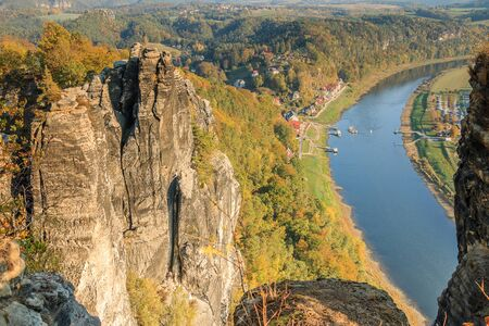 Lookout point from the Bastei into the Elbe valley to the town of Rathen. Autumn mood in Saxon Switzerland. Rock formation in sunshine with a view of the river Elbe