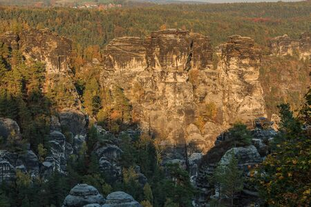 Saxon Switzerland National Park with trees and rocks. View of forest with trees from the Elbe Sandstone Mountains in autumn mood. Rock formation in the evening sun and a blue sky