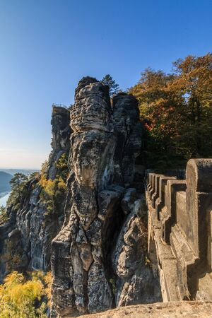 Partial view of the Bastei bridge. Saxon Switzerland with rocks and trees in autumn mood on the terrace view of the Elbe Sandstone Mountains with blue sky and sunshine