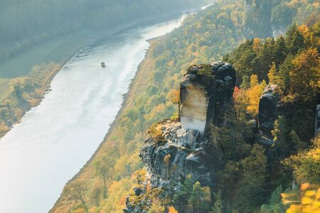 River course of the Elbe in Saxon Switzerland in autumn. Rocks with stones and forests in the sunshine. Boat on the river in the Elbe valley. Trees in seasonal colors 版權商用圖片