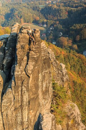 Rocks for climbing in the Saxon Switzerland National Park. Elbe Sandstone Mountains with rock formation, forests in seasonal colors and houses in autumn. View from the Bastei bridge