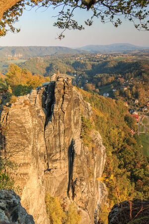 Rocks for climbing in the Saxon Switzerland National Park. Elbe Sandstone Mountains with rock formation, forests in seasonal colors and houses in autumn. View from the view of the Bastei bridge