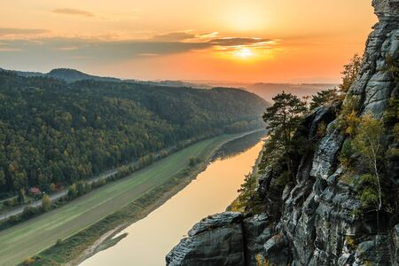 View of the Elbe valley in the Saxon Switzerland National Park. River Elbe at sunset. Colorful sky with yellow-red sun. Landscape with rocks, trees and forests in autumn mood
