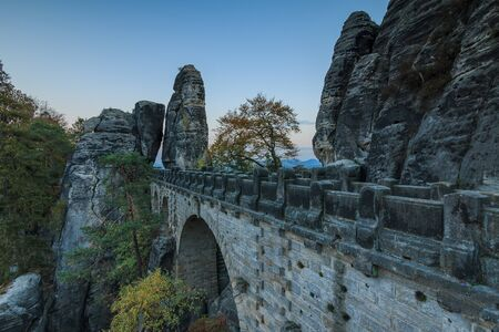 Side view of  Bastei Bridge in the Saxon Switzerland National Park. Footpath in the evening with rock formation. Blue sky with trees and forests. Landscape in autumn mood