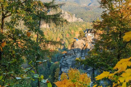 View of a rock formation in Saxon Switzerland. National park in the Elbe Sandstone Mountains for hiking and climbing in autumn mood. Evening sun with trees and blue sky