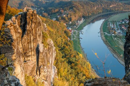 Autumn mood in the Saxon Switzerland National Park. Rock formation and forests in the evening sunshine with a view of the Elbe from the viewpoint of the Bastei Bridge
