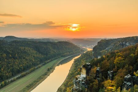 Saxon Switzerland National Park with the Elbe Valley .. Landscape with a view from Bastei Bridge with the Elbe and rocks, trees and forests in the autumn mood with an orange horizon at sunset 版權商用圖片