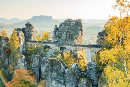 Historic Bastei bridge in Saxon Switzerland in autumn. Rocks and trees with blue sky and sunshine. Elbe valley with mountains in the background