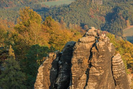 Autumn landscape with climbing rocks in the Saxon Switzerland National Park. Elbe Sandstone Mountains with rock formation, forests in seasonal colors and houses in autumn. View from Bastei bridge 版權商用圖片
