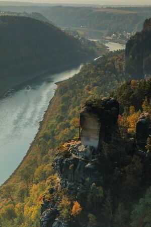 River Elbe in Saxon Switzerland in autumn mood. Rocks with stones and forests in the sunshine. Boat on the river in the Elbe valley. Trees in seasonal colors 版權商用圖片