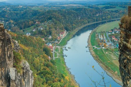 View of the Elbe valley from the Bastei bridge in the evening. View of the spa town of Rathen. Rocks and trees in autumn. Buildings, ship and ferry on the river 版權商用圖片