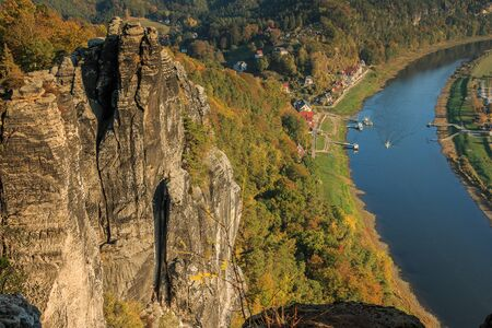 View from the Bastei bridge into the Elbe valley in the town of Rathen. Autumn mood in the National Park of Saxon Switzerland. Rock formation in the sunshine with a view of the Elbe