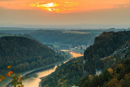 Magnificent sunset with a view over the Elbe valley in the Saxon Switzerland National Park. Landscape of the Bastei bridge with rocks, trees and forests in the autumn mood with an orange horizon