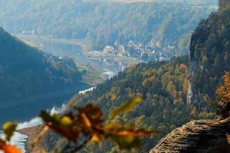 View of the Elbe valley in Saxon Switzerland. River course with sunshine and trees in autumn. Rocks and buildings in daylight in the Elbe Sandstone Mountains in Germany