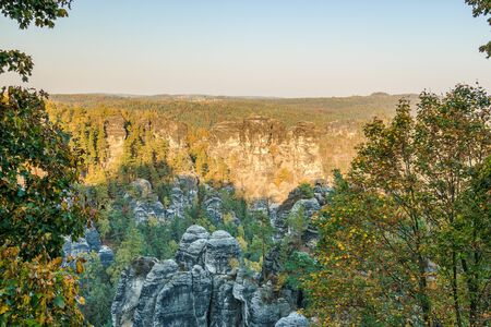 Rocks and forests in Saxon Switzerland. Elbe Sandstone Mountains in the National Park in Saxony for the autumn mood. View of the rock formation in the evening sun and blue sky 版權商用圖片