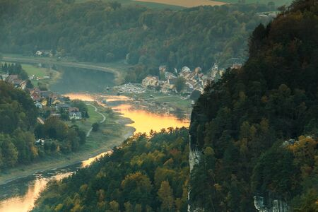 View of the village of Wehlen in the valley in the Saxon Switzerland National Park. River Elbe with trees and rocks in the autumn mood. Sunshine from the sunset is reflected in the water 版權商用圖片
