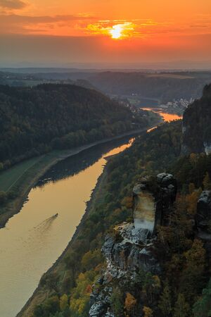 Landscape of Saxon Switzerland National Park with the Elbe Valley in the evening. View from the Bastei bridge with the Elbe and rocks, trees and forests in the autumn mood with an orange sunset