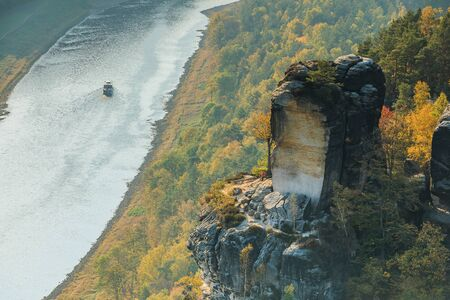 River Elbe in Saxon Switzerland for autumn mood. Rocks with stones and forests in sunshine. Boat on the river in the Elbe valley. Trees in seasonal colors