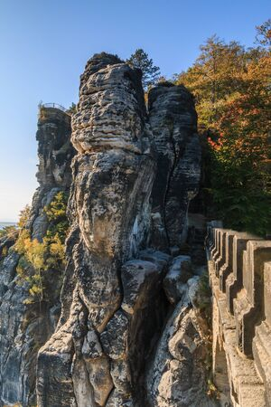 Lateral view of the Bastei bridge in Saxon Switzerland. Rocks and trees in autumn mood with a terrace view of the Elbe Sandstone Mountains with blue sky and sunshine