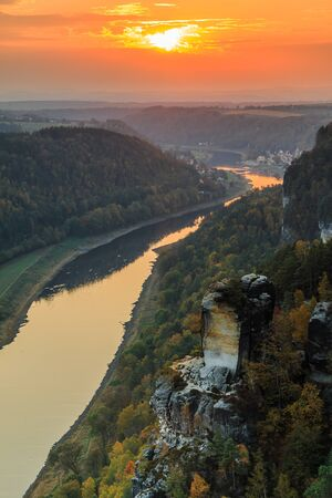 Landscape in Saxon Switzerland with the Elbe valley in the evening. National park with a view from the Bastei bridge with the Elbe and rocks, trees and forests in the autumn mood with an orange horizon at sunset 版權商用圖片