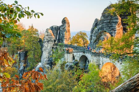 Bastei bridge in Saxon Switzerland. Historic buildings in the National Park of Saxony. Rock with footpath in the evening in autumn mood. Green, brown and yellow leaves of the trees 版權商用圖片