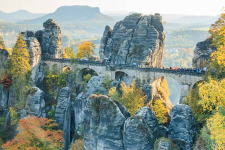 Bastei bridge in Saxon Switzerland in autumn mood. Rocks and trees with blue sky and sunshine. Elbe valley with mountains in the background