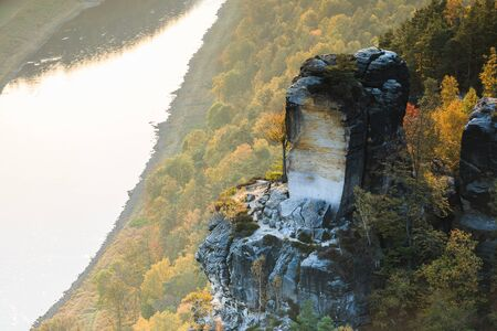 Elbe in the National Park Saxony in autumn. River course and rocks with stones and forests in the sunshine in Saxon Switzerland. Sunset on the horizon over the Elbe valley
