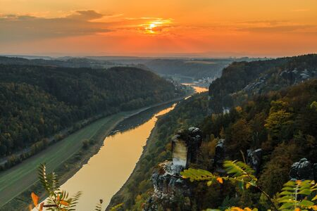 View from the Bastei bridge over the Elbe valley in the Saxon Switzerland National Park. Elbe river at sunset. Landscape with rocks, trees and forests in autumn mood with orange horizon