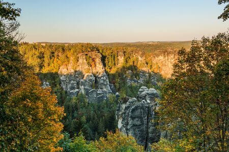 Rocks and forests in Saxon Switzerland. National Park in the Elbe Sandstone Mountains in autumn mood. View of rock formation in the evening sun and a blue sky