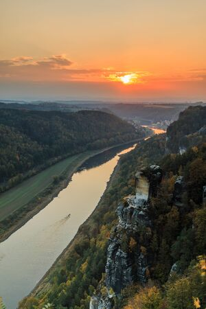 Saxon Switzerland with the Elbe valley in the evening. National park with a view from the Bastei bridge with the Elbe and rocks, trees and forests in the autumn mood with an orange horizon at sunset 版權商用圖片