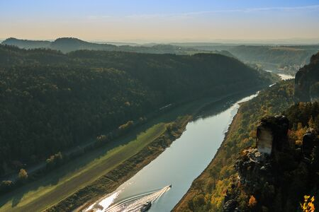 Elbe in the National Park of Saxon Switzerland in autumn mood. Rocks with stones and forests in the sunshine. Boat and ship on the river in the Elbe valley. Trees in seasonal colors