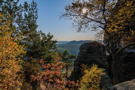 Saxon Switzerland in autumn. Sunshine with a blue sky through trees with rocks and a view from the Bastei bridge over the valley in the Elbe Sandstone Mountains 版權商用圖片
