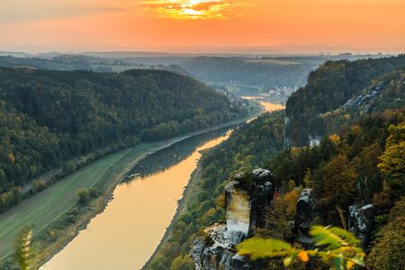 View from the Bastei bridge over the Elbe valley in the Saxon Switzerland National Park. Landscape with Elbe and with rocks, trees and forests in the autumn mood with orange horizon at sunset