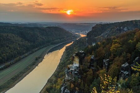 Saxon Switzerland with the Elbe valley in the evening. Landscape in the national park from the Bastei bridge with the Elbe and rocks, trees and forests in the autumn mood with an orange horizon at sunset