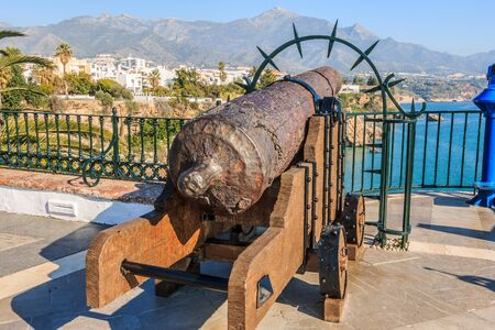 Point of interest from the balcony Europe on the Spanish coast of Nerja. Old historical cannon on the Costa del Sol with a view of the Mediterranean Sea with blue sky. Beach course in the background