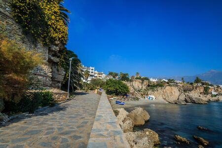 Coastline with footpath on the Mediterranean Sea of the Spanish Costa del Sol. Small beach in Nerja with rocks and blue water on sunny day with blue sky, flowers and bushes 版權商用圖片