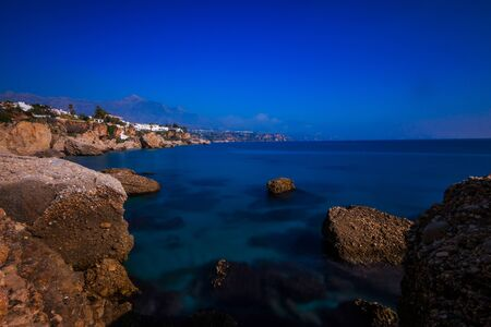 Beach section on the Spanish coast of Costa del Sol in Nerja. Sunny day with blue Mediterranean waters with rocks and city in the background