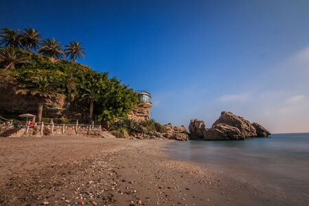 Small sandy beach on the Spanish coast of Costa del Sol. Balcon Europa in Nerja on sunny day as a view over the Mediterranean. View of rocks with palm trees and lifebuoy