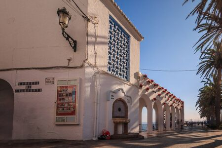 Historic house in Nerja on the street to the view Balcon of Europe. House with arches and flower pots on the wall and hallways with blue sky in sunshine and Santa Claus on floor