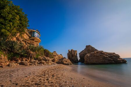 Sandy beach on the Spanish coast of the Costa del Sol. Viewpoint Balcon Europa in Nerja on sunny day as a view over the Mediterranean. View of rocks with palm trees and rocks on the beach