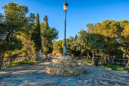 Gibralfaro in Malaga. Lookout point with paved footpath and central street lamp on sunny day surrounded by conifers and cypresses with blue sky