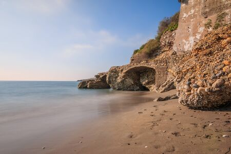 Beach section on the Mediterranean coast in Nerja. Sandy beach on the Spanish coast of Costa del Sol with rocks and stone arch on sunny day with blue sky and clouds 版權商用圖片