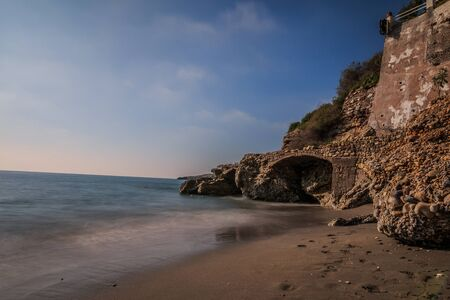Section of beach in Nerja. Sandy beach on the Spanish coast of Costa del Sol with rocks and stone arch on sunny day with blue sky and clouds. Calm Mediterranean sea with buildings