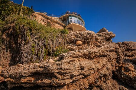 Balcon de Europa in Nerja on a sunny day. Lookout platform on the Spanish Mediterranean coast with blue sky. Buildings on a rock with stones and palm trees