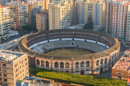 Bullring on the coast of Malaga. In the center of Malaga amid high-rise buildings with a view over the roofs over the city with sunshine and blue skies, trees and bushes 新聞圖片